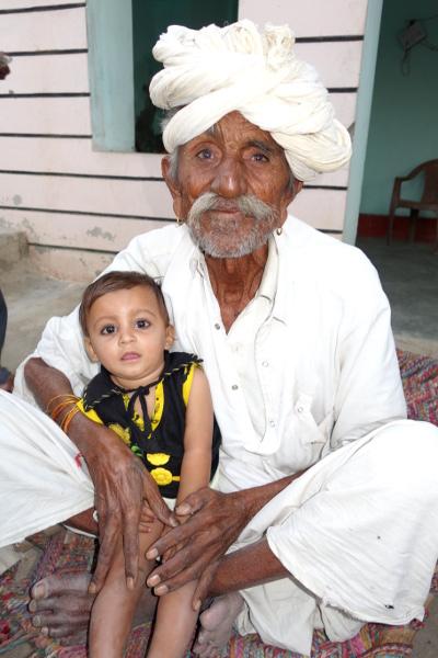 """Au sortir du village, à la périphérie, une famille m'invite à entrer dans leur demeure pour me présenter le patriarche. Ce vieil homme avec son arrière petit-fils dans son giron est de la caste des Meghwals. C'est une caste considérait comme très inférieure dans la hiérarchie des castes. Ce sont ces gens qui sont qualifiés d' """"Intouchables"""". Mais je remarque que les membres de cette famille connaissent une évolution positive. La maison est en dur et plutôt confortable. L'un des fils est ingénieur. Des politiques de promotion sociale mises en place depuis l'Indépendance permettent de réelles progressions sociales."""