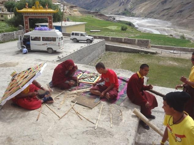 Les jeunes moines fabriquent des ornements et objets divers en vue de la cérémonie à venir