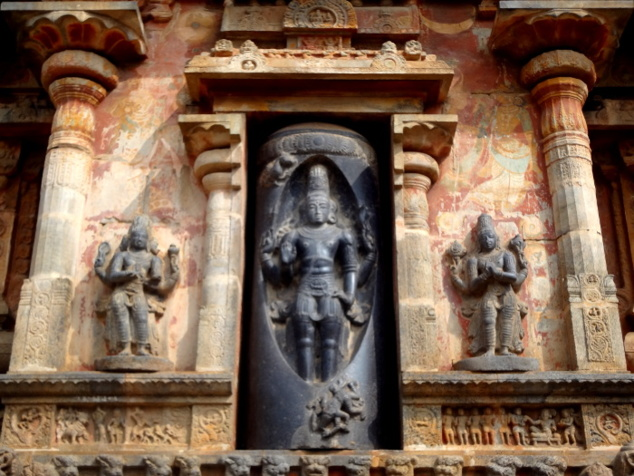La statue du maître des lieux sculptée dans un monolithe noir. On peut distinguer de part et d'autre des traces de fresques colorées.