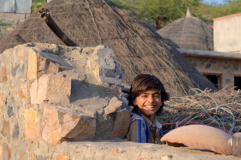 """Il y a dans ce village un mélange de maisons en dur et huttes traditionnelles. Comme un mélange de tradition et de modernité. Il y a cet enfant qui reste à l'écart. Qui est-il ? J'apprends que les """"dominants"""" dans ce village sont des Rajpouts (à l'origine un clan guerrier) et nous recontrerons des Manganiyar (musiciens/chanteurs) et des Meghwals."""