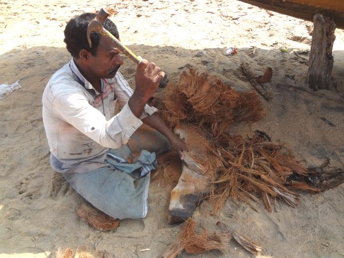 Préparation de l'étoupe à l'aide de fibres de noix de coco qui permettra d'étanchéiser la coque.