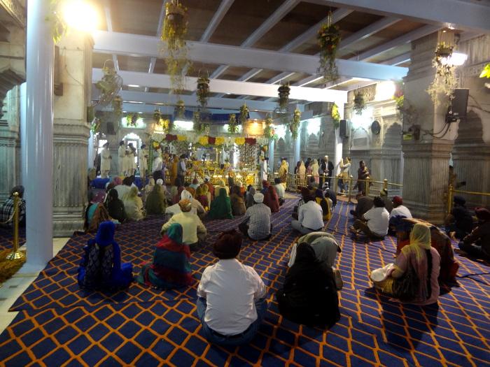 """Dans le même quartier, un grand temple sikh ou """"gurdwârâ"""". Ici la salle de prière où l'on s'incline devant le livre sacré, le """"Guru Granth Sahib"""", considéré comme le gourou de la communauté. A noter qu'hommes et femmes sont assis côte à côte. Le sikhisme prône l'égalité sociale et rejette les castes."""